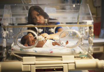 Nurse tending to infant in incubator.